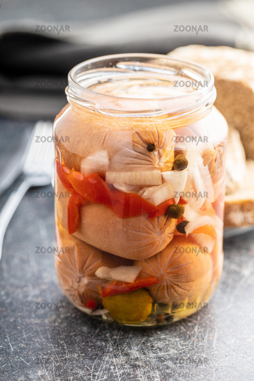 Pickled sausages with onion and red pepper. Marinated food.