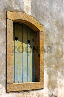 Historic church window in colonial style with stone frame