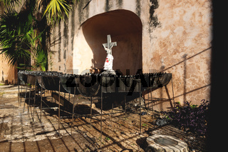 Jesus statue surrounded by candle holders at the Convent de San Bernardino de Siena with grass field in Valladolid, Yucatan, Mexico