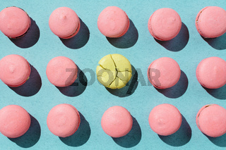 Pink and yellow vegan macaroons arranged on pastel blue background