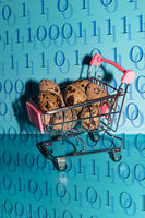 A small shopping cart with quail eggs and blurred binary numbers as foreground. Concept of shopping, money, coding, business, cyber, online and etc. E-Commerce And Online Purchases: Keyboard And Shopping Cart