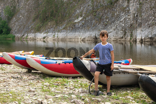 Boy tourist outdoors pumps catamaran with foot-powered pump. Schoolboy on summer vacations, school camp and youth outdoor activities.