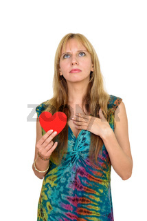 Portrait of beautiful blonde woman thinking while holding heart