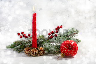 Burning red candle with snow fir branches. Christmas advent.