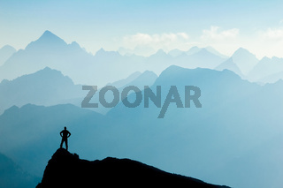 Man reaching summit after climbing and hiking enjoying freedom and looking towards mountains silhouettes panorama during sunrise.