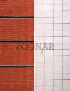a brick red brick wall with black lines divided in half by large white modern stone tiles