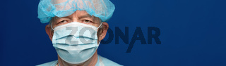 Experienced senior adult doctor dressed medical face surgical mask and cap. Preventive protection against contagious disease, coronavirus