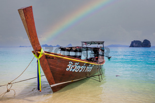 Longtail boat on beach in Thailand with rainbow