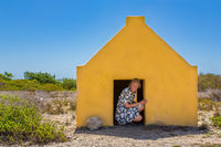 Woman entering yellow slave house at coast