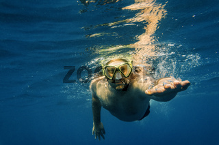 Male diver in blue water. Open sea, ocean, swimming, active travel and underwater diving concept.