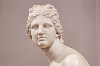 Ancient white marble sculpture head of young woman. Statue of sensual renaissance art era naked woman antique style