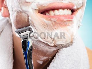 Handsome man shaving with razor