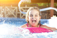 Happy girl playing in swimming pool