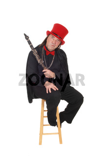 A clarinet player with a red hat and black outfit pointing up