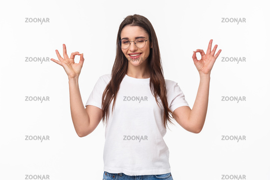 Waist-up portrait of confident sassy young attractive girl in glasses, wink cheeky and smiling reassuring all good, no problem, guarantee everything under control, smile and make okay signs