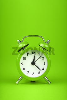 Close up one green alarm clock over green background