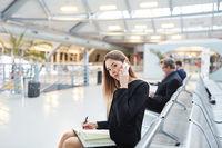 Geschäftsfrau mit Smartphone im Flughafen Terminal