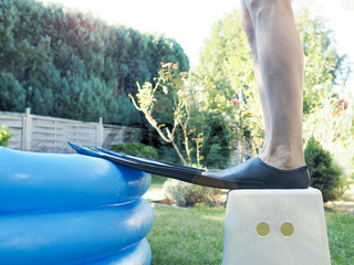 Man with flippers stands in front of a small inflatable pool.