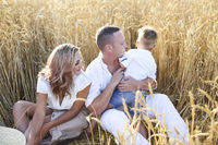 Happy family with happy son in the summer sunset field