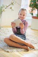 Mädchen mit Tablet PC zu Hause