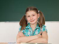 Schülerin sitzt im Klassenzimmer an einem Tisch