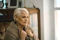 Pensive Senior Woman Wrapping Herself In A Warm Sweater Siiting On The Cosy Sofa