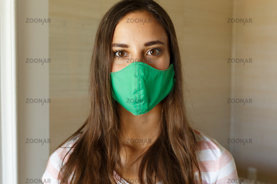 Portrait of caucasian woman wearing green face mask looking straight to camera