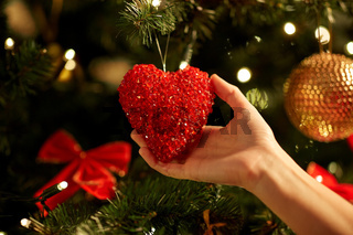 hands decorating christmas tree with red heart