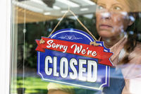 Sad Female Store Owner Turning Sign to Closed in Window