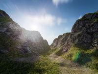 The sun rises over a path through a mountain landscape. Nature, adventure or exploration concept background.