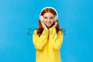 Waist-up shot sassy good-looking redhead, ginger girl with blue eyes and freckles in soft yellow sweater, listen music headphones, press earphones to ears, smiling hear new song favorite singer