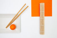 Top View Of White Empty Sushi Plates With Bamboo Chopsticks and Golf Ball.