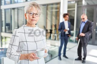 Ältere Geschäftsfrau im Büro mit Tasse Kaffee