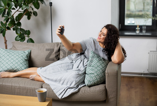 happy woman taking selfie with smartphone at home