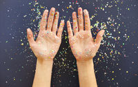 Female hands over table with confetti