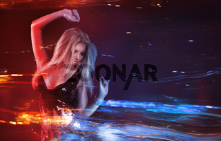 Young blonde woman dancing at night disco club. Wide motion blur with neon light effect