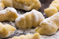 Uncooked homemade potato gnocchi with fork
