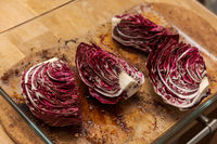 Quartered radicchio in glass casserole dish on wooden kitchen table