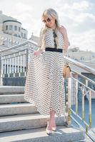 Cute young woman wearing a long dress posing