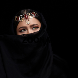 A conceptual middle Eastern portrait of a woman's face decorated with Oriental-style jewelry on a black Studio background.
