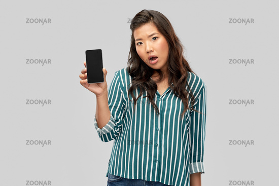shocked asian woman over grey background