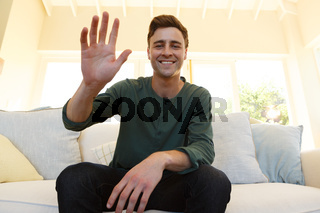 Caucasian man having video call waving and smiling sitting on couch in living room