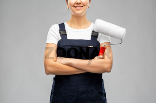 happy female worker or builder with paint roller
