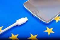 Close up Mobile phone Charger with USB Type - C cord on EU Flag