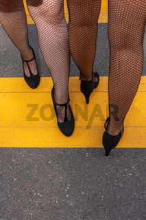 two elegant woman wearing high heeled black shoes