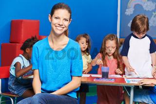 Lächelnde Erzieherin vor Gruppe Kinder