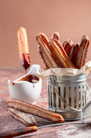 Traditional churros sticks with cinnamon and chocolate.