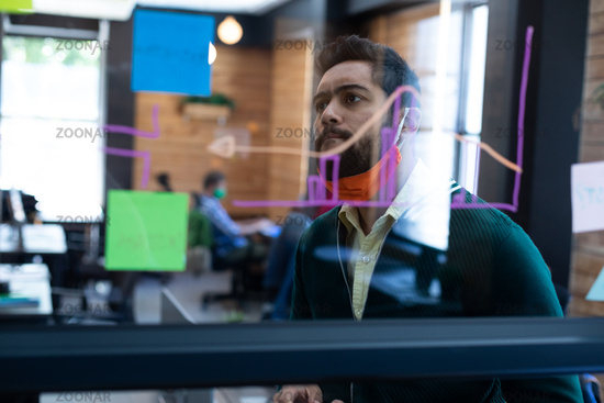 Mixed race man wearing face mask looking at information on glass wall in office