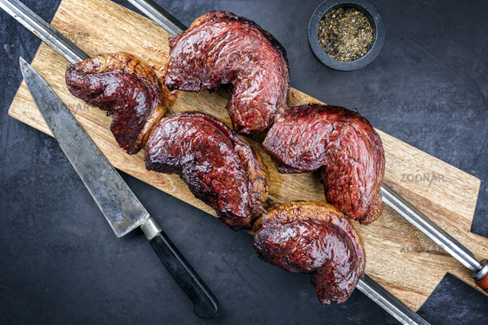 Barbecue dry aged wagyu Brazilian picanha from the sirloin cap of rump beef offered on a skewer on black on a wooden board