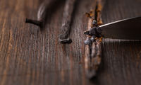 Vanilla beans and seed pods with knife on wooden background.  Preparing vanilla as baking ingredient.